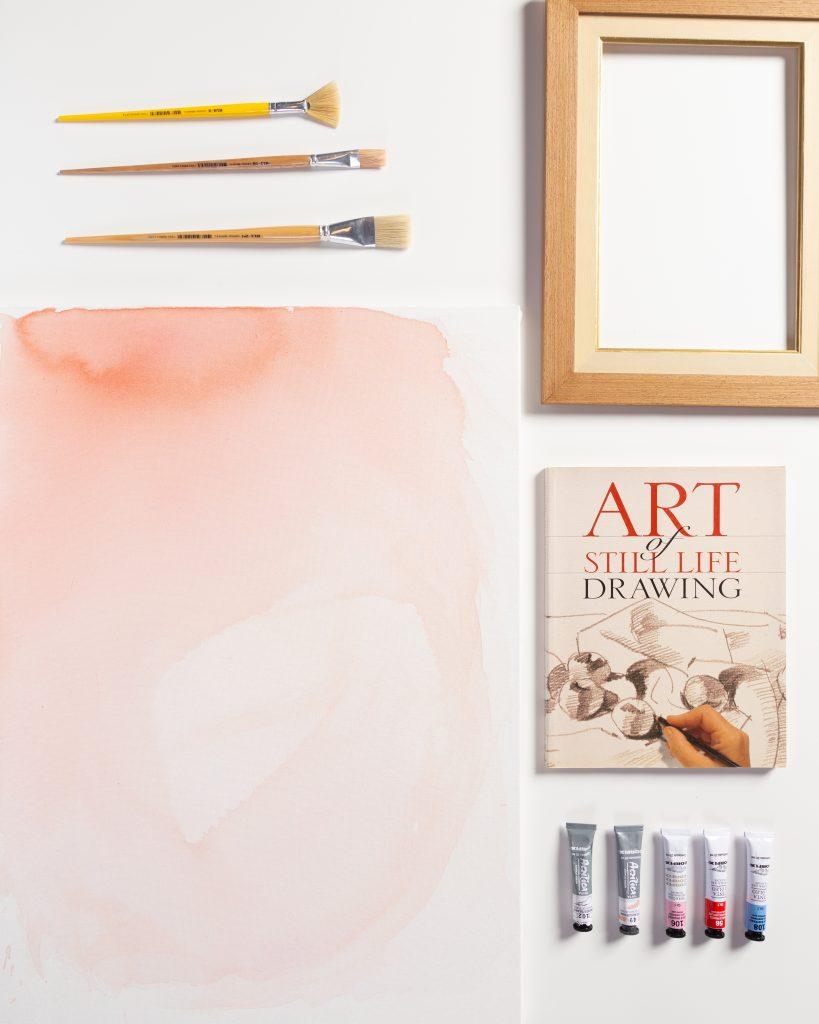 Flat lay de tela de pintura com livro de desenho e pinceeis em fundo branco