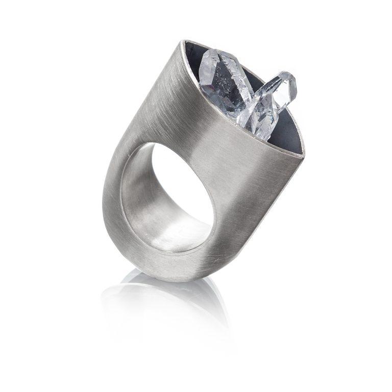 fotografia still de anel em prata com cristais em fundo branco