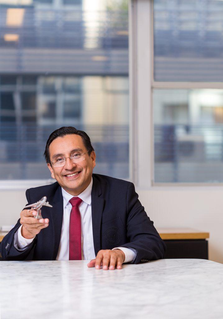 Retrato corporativo de executivo de terno sentado a mesa do escritório segurando um avião de maquete