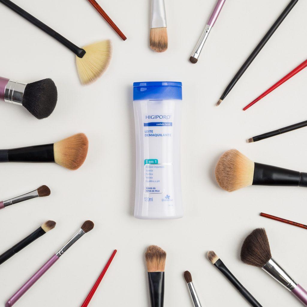 Flat lay de leite demaquilante Higiporo no centro com pincéis de maquiagem em volta em fundo branco