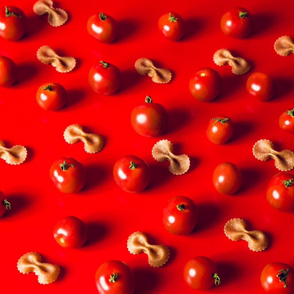 fotografia de alimentos flat lay de composição de tomates cerejas com farfalle em fundo vermelho